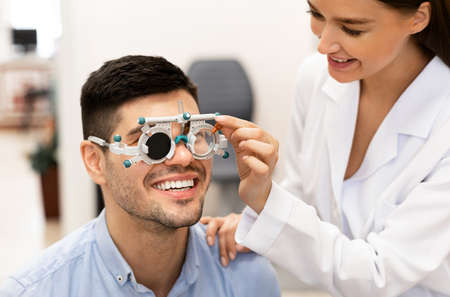 Consultation With The Ophthalmologist Concept. Portrait of woman optometrist examining eyesight of male client with trial frame and closed eye. Woman doing checkup of mans eye with diagnostic tool Standard-Bild