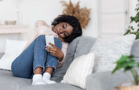 Loneliness. Depressed Black Lady Sitting On Couch With Smartphone, Loking At Device Screen, Feeling Upset And Bored At Home, Having No Friends, Heartbroken Woman Waiting For Message From Boyfriend