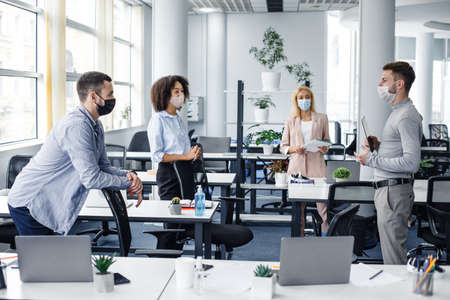 Modern team meeting, group work and social distancing. Manager with tablet speaks with workers in protective masks in interior of modern office with gadgets during coronavirus epidemic, free space Reklamní fotografie