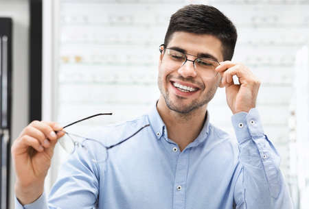 Portrait of happy young man choosing new eyeglasses at optics store, holding and trying on spectacles. Bad Eyesight And Poor Vision Concept. Smiling guy patient looking and picking frame