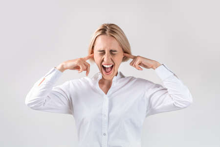 Attractive businesswoman in closing her ears and screaming in anger on light grey studio background. Female corporate employee expressing her rage, feeling furious or having nervous breakdown 版權商用圖片