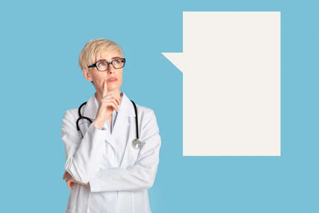 Diagnosis, disease treatment and medical care. Pensive adult female doctor in glasses and coat presses finger to chin and looks up at empty space at abstract place for thoughts, on blue background