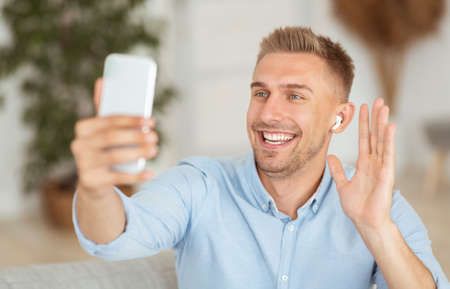 Online Video Call. Portrait of smiling guy making virtual conference, holding mobile phone, wearing wireless earbuds, waving with hand to webcam. Communication Concept. Man chatting using smartphone 写真素材