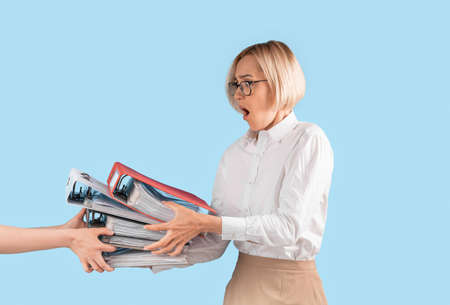 Frustrated office worker taking folders of documents from boss on blue studio background. Exhausted female corporate employee overloaded with papers, stressed over excessive work