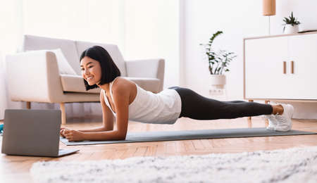 Training At Home. Full length portrait of sporty smiling asian woman doing plank while watching online tutorial on laptop computer, exercising in living room on the floor on yoga mat, free space