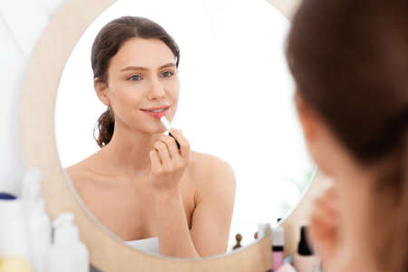 Pretty young woman looking at mirror, using lipstick, bedroom interior, empty space. Attractive lady taking care of her beautiful lips, putting beautiful lipstick at home, applying makeup, closeup
