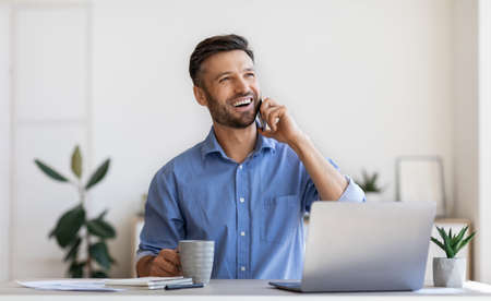 Cheerful Millennial Businessman Relaxing At Workplace In Office With Cellphone And Coffee, Sitting At Desk And Talking On Mobile Phone, Speaking With Family, Having Break At Work, Copy Space