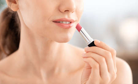 Cropped of young woman using lipstick, bedroom interior, empty space. Side view of unrecognizable lady taking care of her beautiful lips, putting beautiful lipstick at home, applying makeup, closeup