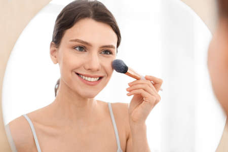 Closeup of attractive young woman applying blush on her face, sitting in front of mirror, copy space. Smiling attractive young lady doing makeup before going out, shot over shoulder in bedroom Stock Photo