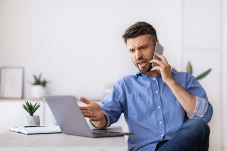 Angry millennial businessman talking on mobile phone and looking at laptop screen working in modern office, having problems with project, annoyed boss speaking with employee by phone, copy space
