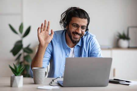 Distant Communication. Happy Western Man In Headset Waving Hand At Laptop Camera While Making Video Call Via Computer In Office, Chatting With Family Or Having Online Conference, Copy Space