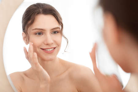 Closeup of cheerful young lady using face cream at home, looking at mirror and smiling. Attractive woman applying beauty product on her cheeks, nourishing her sensitive skin in winter, face care Standard-Bild