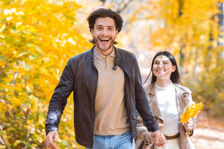 Emotional guy running buy golden autumn forest with his girlfriend, copy space