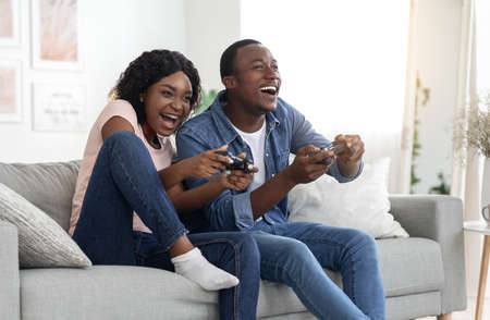 Joyful african american man and woman with joysticks sitting on couch in living room, playing video games and laughing, having fun together at home during lockdown, copy space