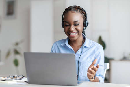 Online Tutoring. Cheerful Black Female Tutor In Headset Having Video Conference With Laptop, Doing Online Training, Talking And Gesturing At Camera During Web Call, Sitting At Desk In Home Office
