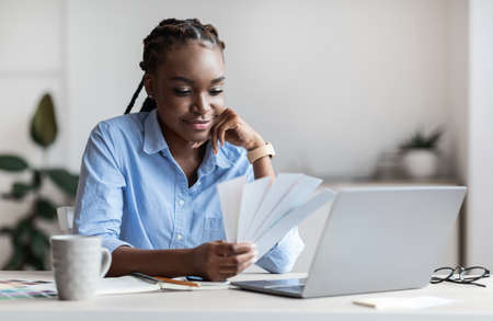 Young african american female designer holding and looking at paper colour swatches, working at desk in white office, black entrepreneur woman choosing color for interior design project, free space