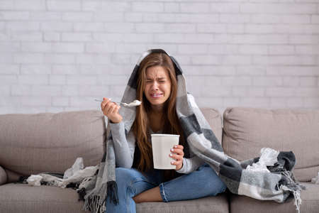 Heartbroken young woman eating ice cream from bucket while watching romantic movie on TV at home. Sad lady crying over breakup or relationship problems, feeling depressed and lonely