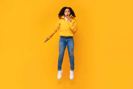 Shocked Black Lady In Winter Jacket Jumping In Mid-Air Covering Mouth With Hand Posing Over Yellow Background. Shocking Offer Advertisement. Studio Shot, Empty Space For Text