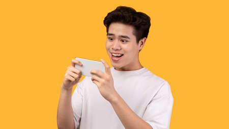 Portrait of excited overjoyed asian guy playing video games on smartphone isolated over yellow studio background, copy space. Satisfied male adult using his gadget