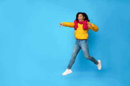 Excited African American Lady Pointing Fingers Jumping In Mid-Air Posing Over Blue Studio Background. Wow Winter Offer, Advertisement Banner. Copy Space For Text