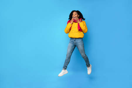 Excited Black Woman In Winter Jacket Jumping In Mid-Air Looking Aside Posing Over Blue Studio Background. Wow Offer, Winter Advertisement Banner, Customers Excitement. Empty Space For Text