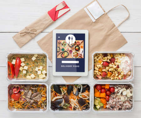 Vegetarian set in ecological packaging. Food with tofu, mussels and vegetables in containers, wooden cutlery and paper bag with tablet food delivery app and menu on screen, top view, flat lay