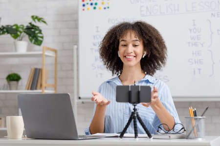 Online English lesson for students in self-isolation at home. Happy african american woman in wireless headphones looks in web camera of smartphone, sitting at table with laptop during covid-19