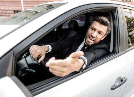 Mad businessman driving luxury car, stuck in traffic, late to airport, copy space. Furious middle-aged man in expensive suit screaming and gesturing to other drivers while driving auto