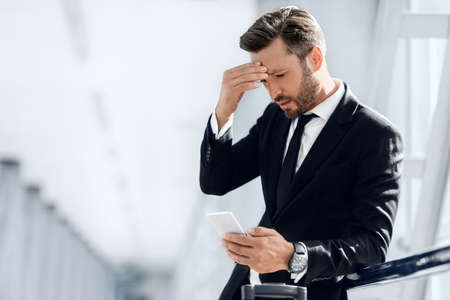 Tired businessman standing by window in airport terminal, using mobile phone, touching his forehead, having headache, copy space. Entrepreneur having business problems, reading emails on smartphone