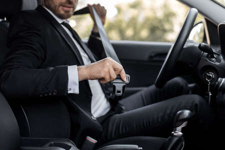 Driving safety concept. Unrecognizable businessman fasten seat belt in his car, ready to go to office. Man in stylish suit putting on his seatbelt before driving car to airport, cropped Stock Photo