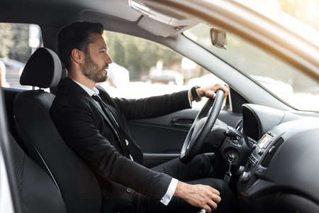 Handsome businessman driving car to airport, going on business side view, copy space. Happy man in stylish suit going to business meeting in the morning, driving his luxury car, shot from cabin Stock Photo