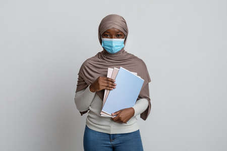 Young black muslim female university student in medical mask with workbooks in hands posing over light studio background, african islamic lady wearing hijab and looking at camera, copy space Banque d'images