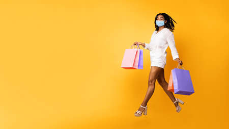 Safe Shopping. Black Woman In Medical Face Mask Running In Mid-Air Carrying Colorful Shopper Bags Posing Over Yellow Background. Studio Shot, Panorama With Copy Space For Text