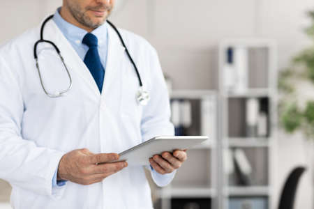 Medical Care And Technology Concept. Closeup of unrecognizable general practitioner holding and using digital tablet, standing at his office in clinic or hospital. Copy space, blurred background