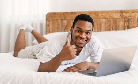 I Like Distant Job. Black Man With Laptop Gesturing Thumbs Up, Working On Computer Online Lying In Bed At Home, Smiling To Camera. Freelance Career And Lifestyle, Remote Job Concept. Selective Focus