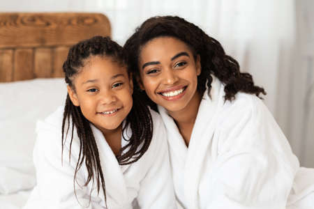 Home Portrait Of Happy African American Mom And Daughter In White Bathrobes Posing At Camera While Relaxing On Bed After Taking Bath, Enjoying Domestic Spa Treatments, Selective Focus, Closeup