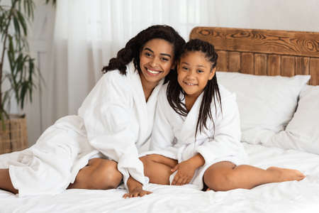Mom And Daughter Relax. Portrait Of Happy Little Black Girl And Her Mother Wearing White Bathrobes Posing On Bed, Relaxing After Home Spa Beauty Treatments, Looking At Camera And Smiling, Copy Space Archivio Fotografico