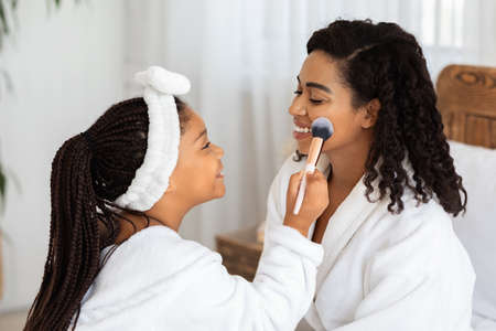 Cute Little Black Girl Applying Makeup With Brush To Her Beautiful Mom, Loving Family Playing Beauty Salon At Home, Happy African Mother And Daughter Wearing White Bathrobes And Smiling To Each Other