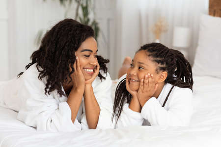 Mother Daughter Love. Little Black Girl And Her Mom Lying On Bed In Bathrobes, Looking At Each Other And Smiling, Resting Head On Hands, Relaxing In Cozy Living Room At Home, Closeup Shot