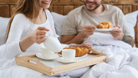 Romantic breakfast at home or hotel in bed for two during quarantine or honeymoon. Happy young husband and wife eating croissants and pouring coffee in cup, at interior of bedroom, cropped, close up