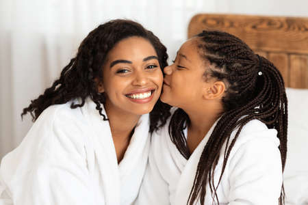 I Love You, Mommy. Little Black Girl Kissing Mom While They Relaxing In Bathrobes At Home After Bath, Cute Child And Mother Bonding Together, Enjoying Domestic Spa Beauty Treatments, Closeup Archivio Fotografico