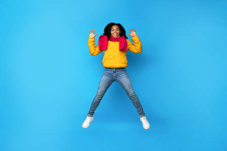 Hello. Joyful African American Woman Jumping Waving Hands In Mid-Air And Smiling To Camera Posing Wearing Warm Jacket Over Blue Studio Background. Winter Advertisement Banner. Full Length Shot