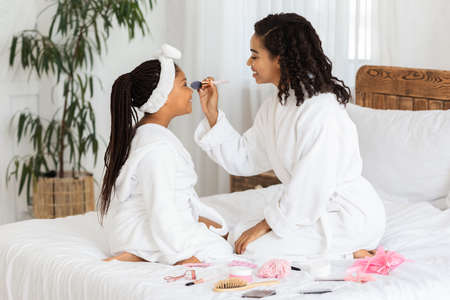 Loving young black mother doing makeup to her little daughter at home, sitting in bathrobes on bed with lots of cosmetics around, having fun together, enjoying domestic beauty spa day, free space