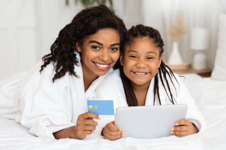 Online Payments. Black Mother And Daughter In Bathrobes Posing With Digital Tablet And Credit Card, Lying On Bed At Home, Shopping In Internet, Ordering Food And Relaxing In Bedroom, Free Space Archivio Fotografico