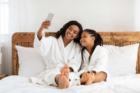 Spa Day Fun. Cheerful Black Mother And Little Daughter In Bathrobes Taking Selfie On Bed At Home, Relaxing Together After Bath, Capturing Self-Portrait On Smartphone, Smiling At Camera, Copy Space Archivio Fotografico