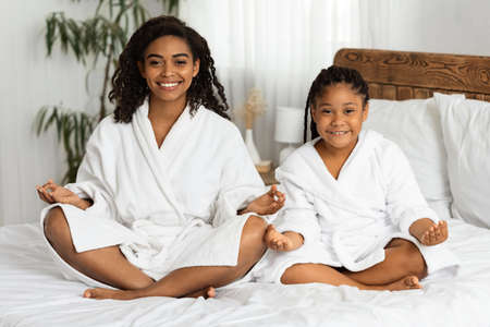 Wellness Day. Cheerful African American Mom And Daughter In Bathrobes Sitting In Lotus Position, Practicing Yoga Together After Bath, Meditating On Bed In Cozy Room, Smiling At Camera, Copy Space