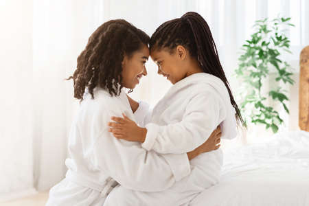 Portrait Of Happy Embracing Black Mom And Daughter In Bathrobes At Home, Bonding With Each Other, Touching Foreheads, Having Fun And Enjoying Spending Time Together, Side View With Copy Space