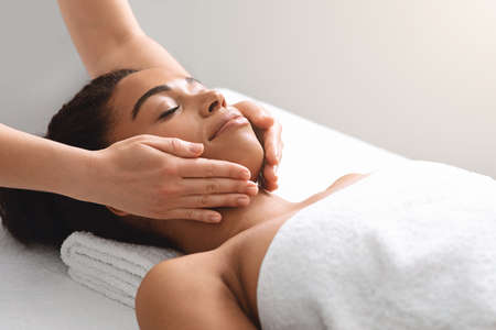 Masseuse hands massaging relaxed black lady face, anti-aging session. side view. African american woman wrapped in towel having relaxing therapy at newest luxury spa salon, spending her weekend at spa