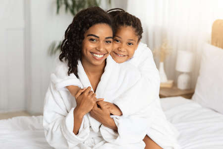 Home Portrait Of Happy Black Mommy And Daughter Wearing Bathrobes And Cuddling, Posing At Camera While Relaxing On Bed After Home Spa Treatments, Having Fun Together, Enjoying Time With Each Other