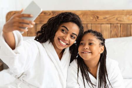 Cheerful African Mother And Daughter In Bathrobes Taking Selfie On Smartphone At Home, Having Fun Together, Taking Photo While Relaxing On Bed After Bath, Enjoying Spa Day, Smiling At Camera Archivio Fotografico